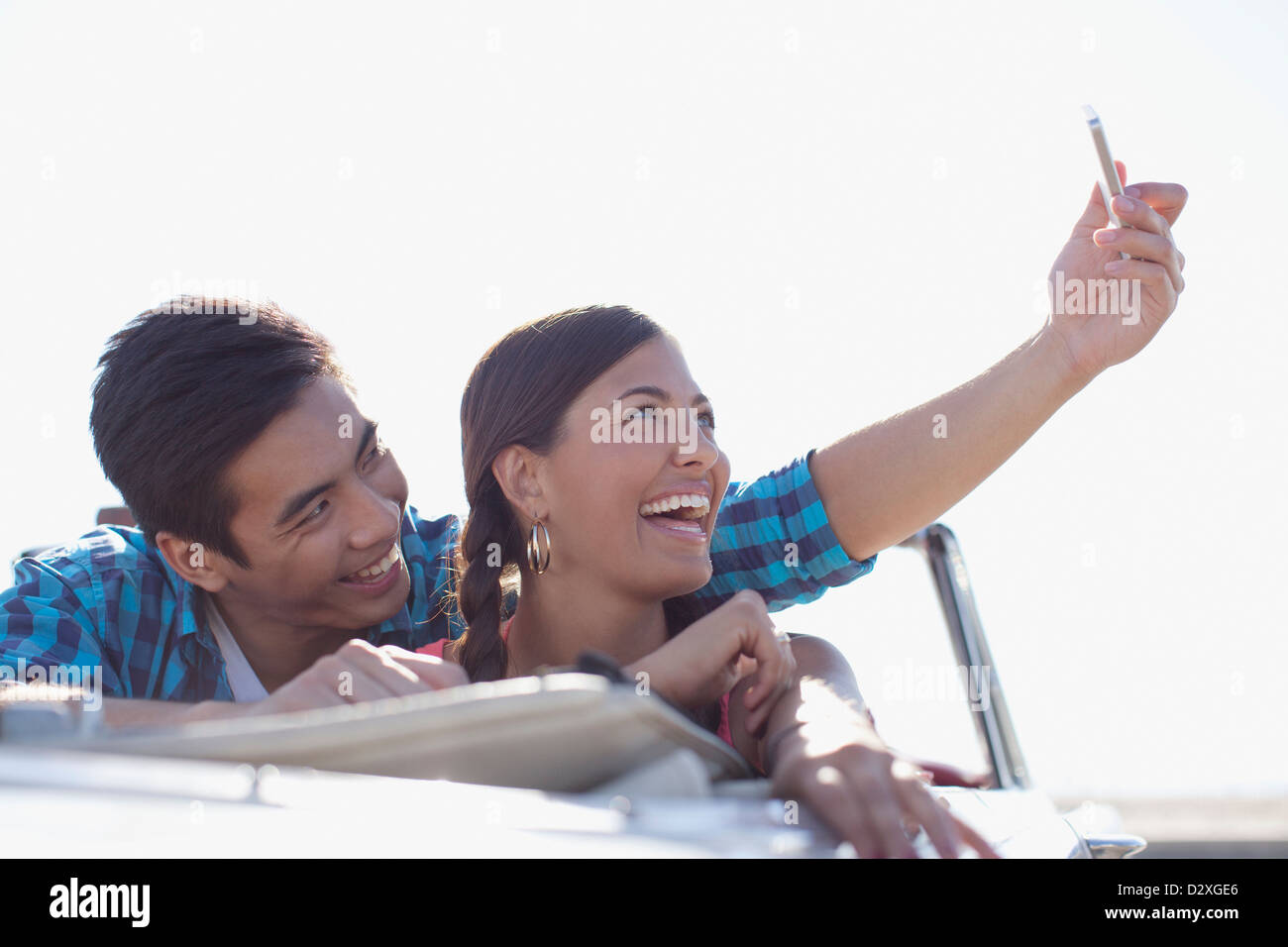 Smiling couple taking picture of themselves - Stock Image