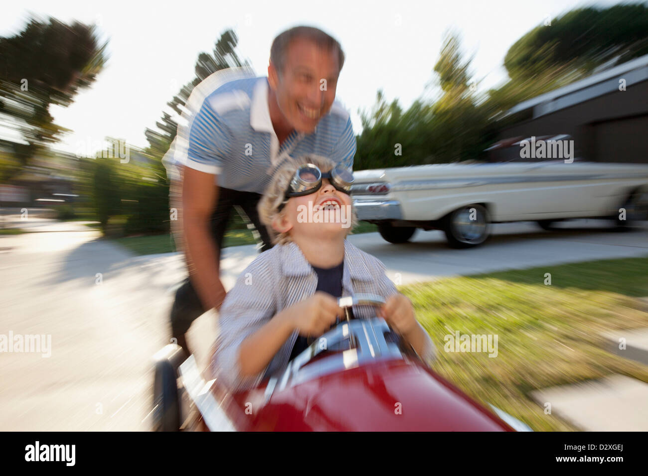 Time lapse view of father pushing son in go cart - Stock Image