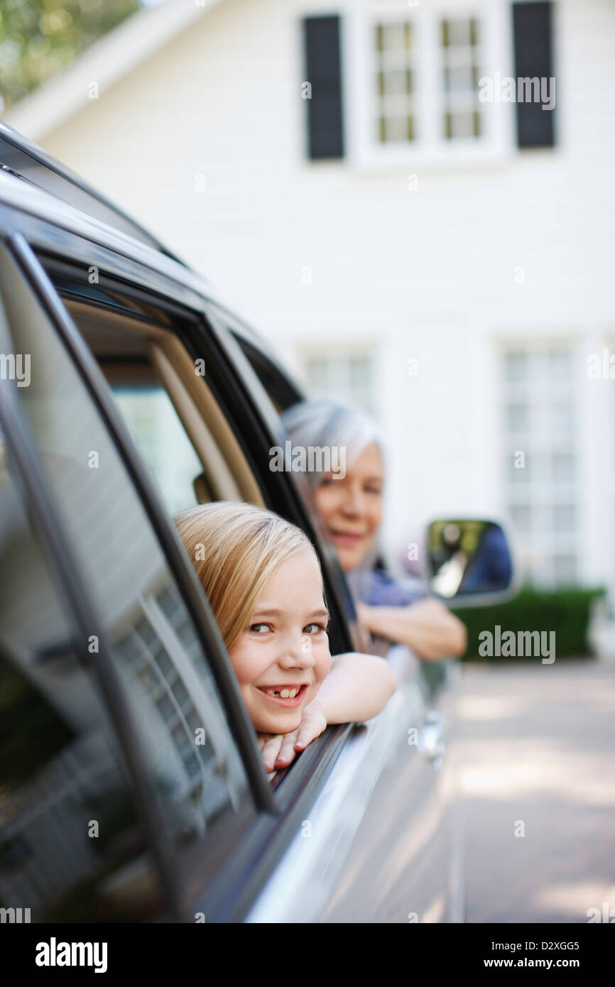 Older woman and granddaughter leaning out car windows - Stock Image