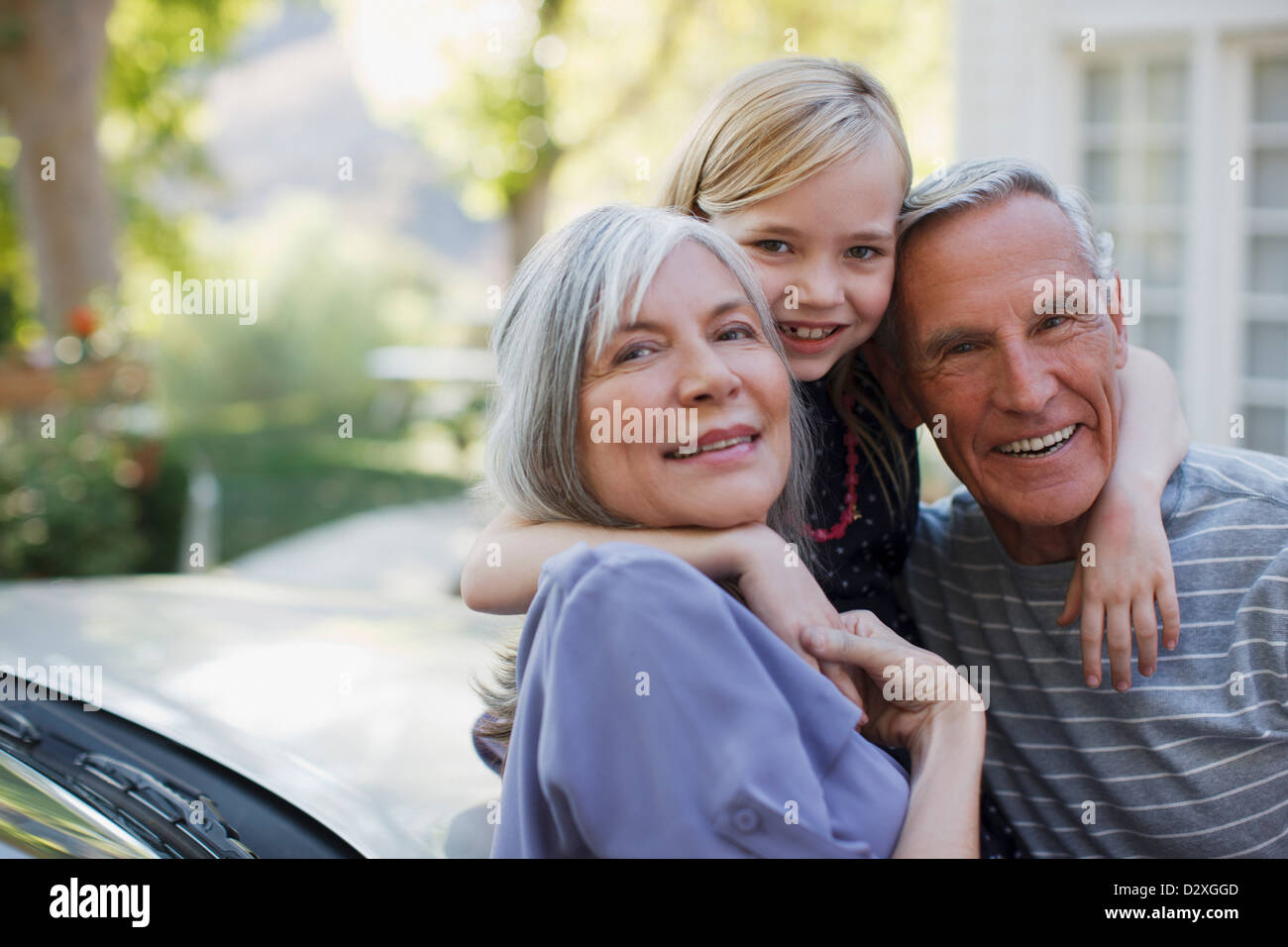 Older couple hugging granddaughter - Stock Image