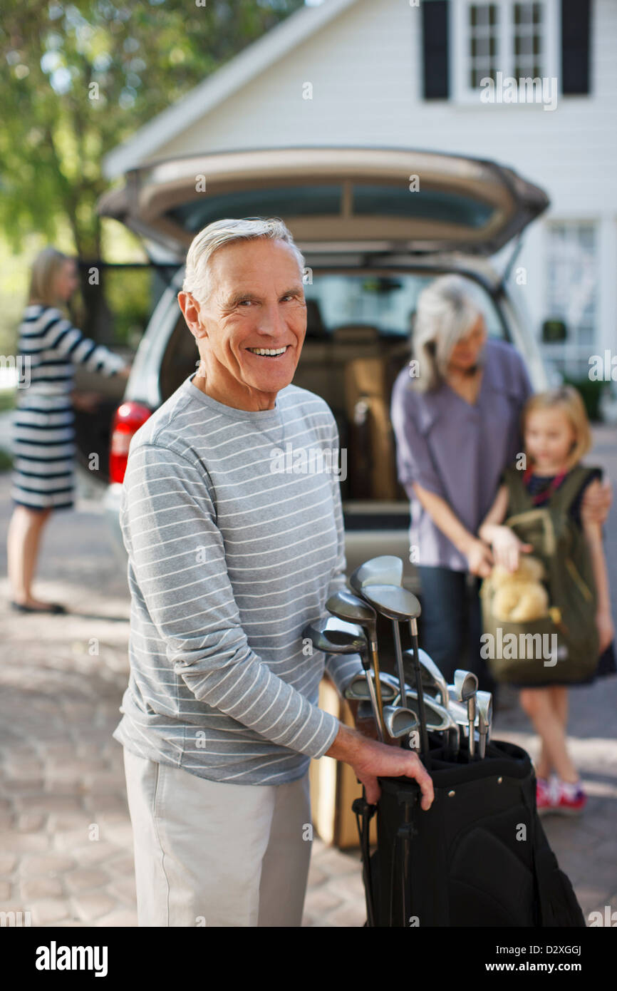 Older man carrying golf clubs in bag - Stock Image