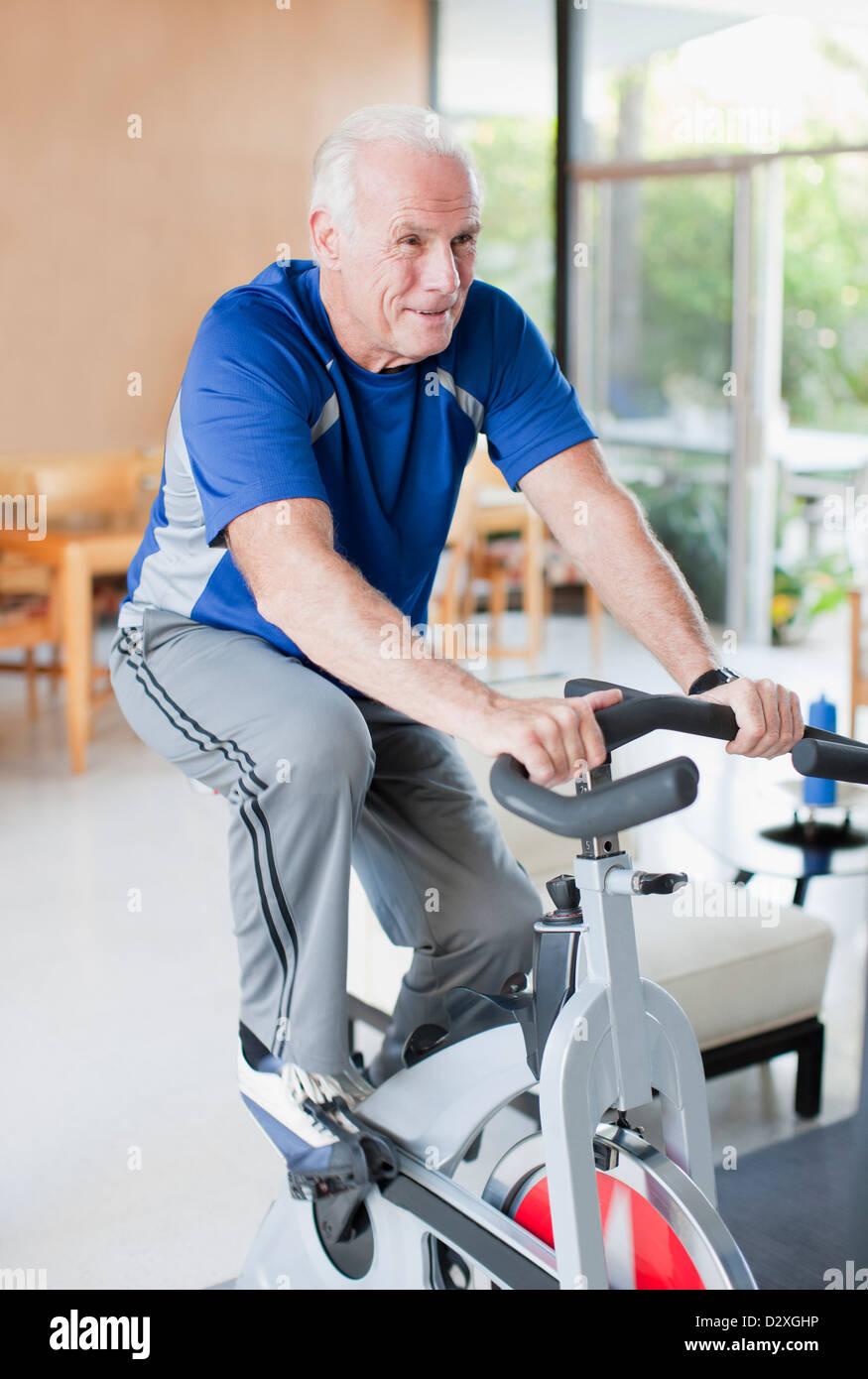 Older Man Riding Exercise Bike At Home Stock Photo