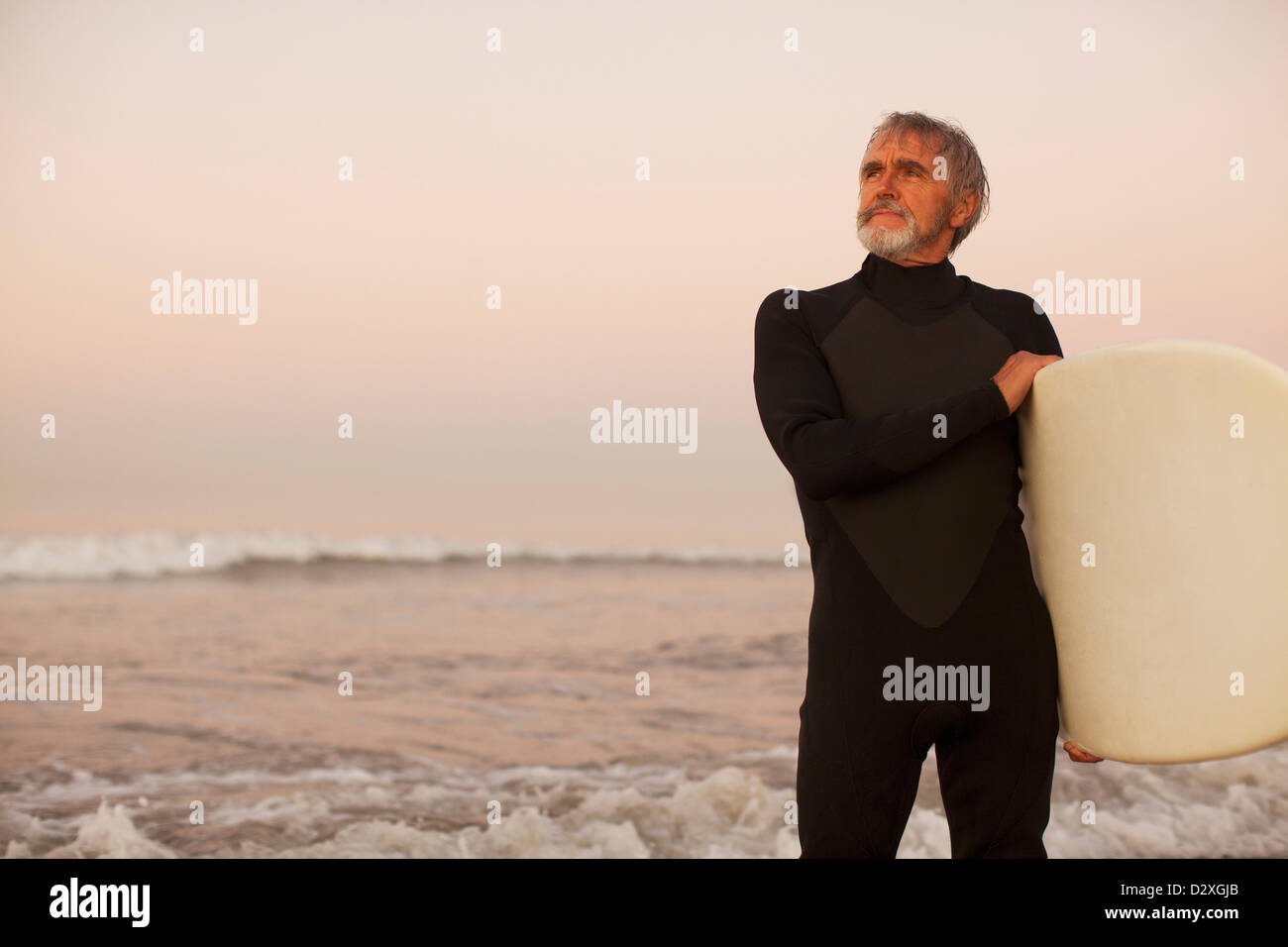 Older surfer carrying board on beach - Stock Image