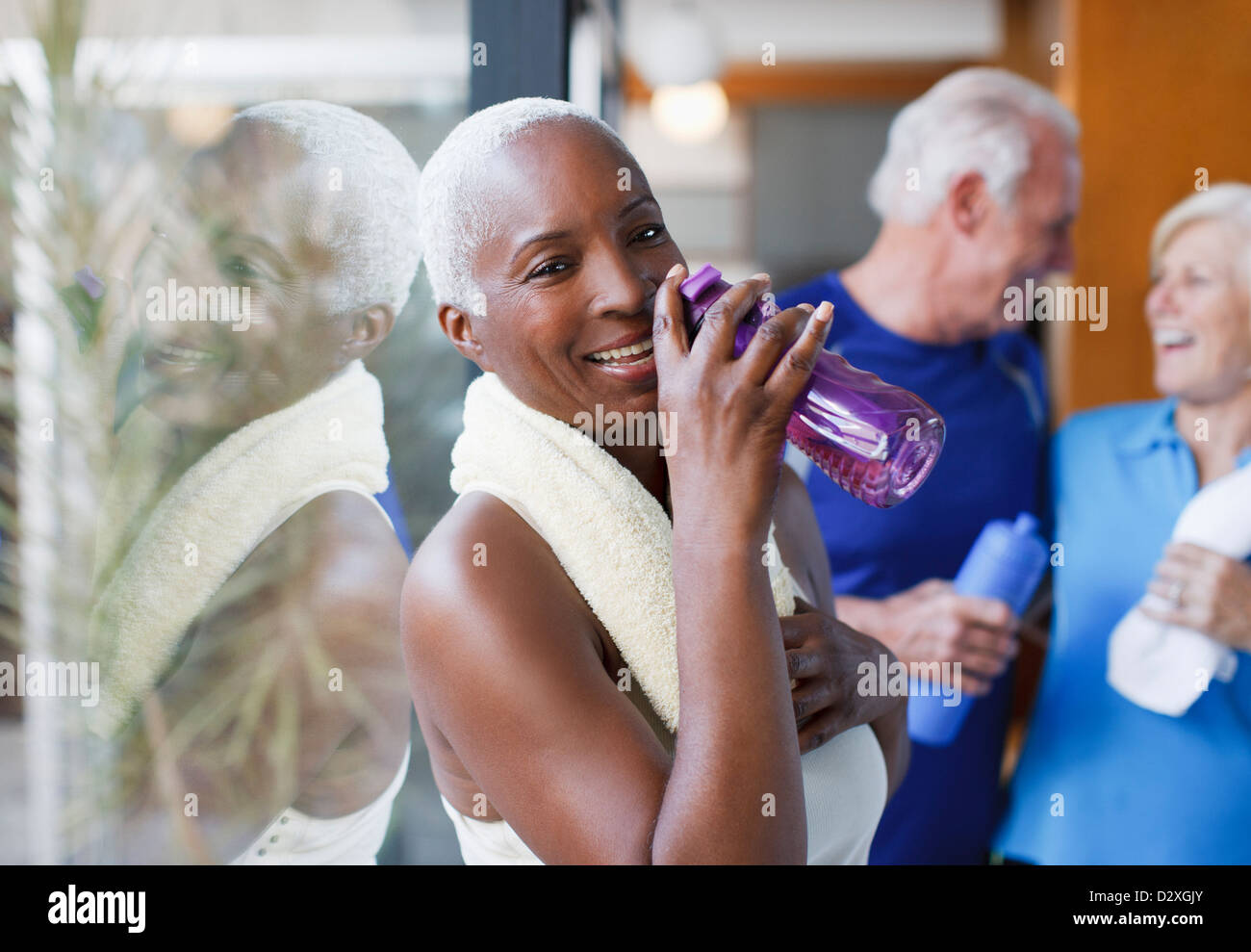 Older woman drinking water after workout Stock Photo