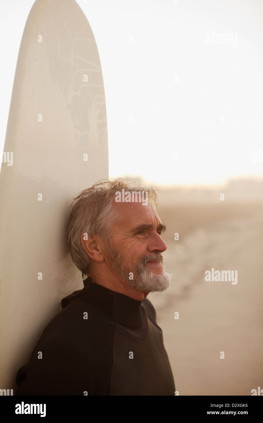 Older surfer leaning on board on beach - Stock Image