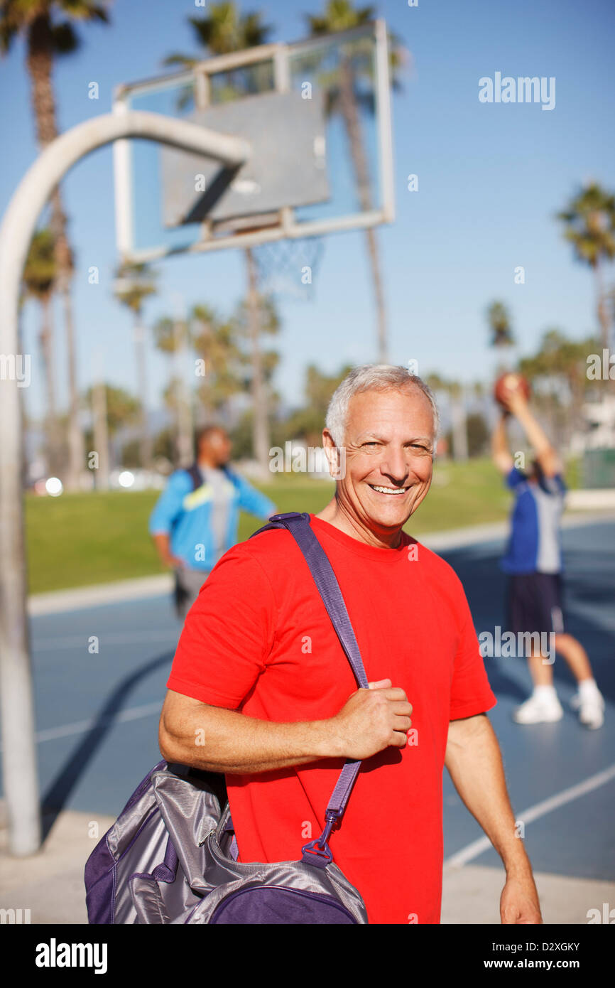 Older man carrying gym bag on court - Stock Image