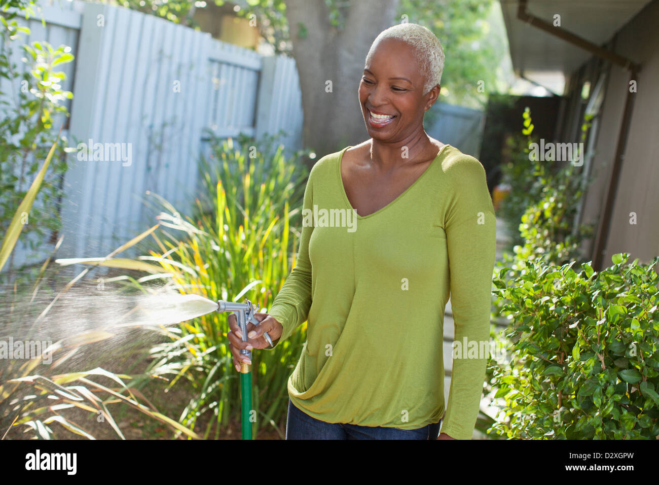 Older woman watering plants on beach - Stock Image