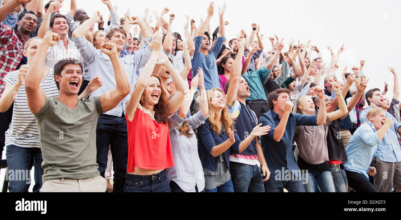Cheering fans in crowd - Stock Image
