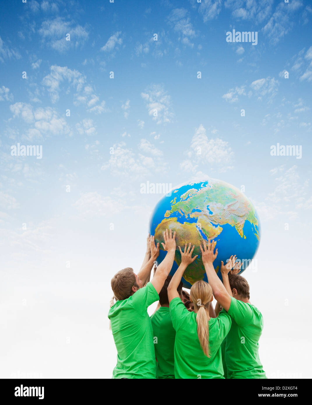 Team in green t-shirts lifting globe overhead - Stock Image