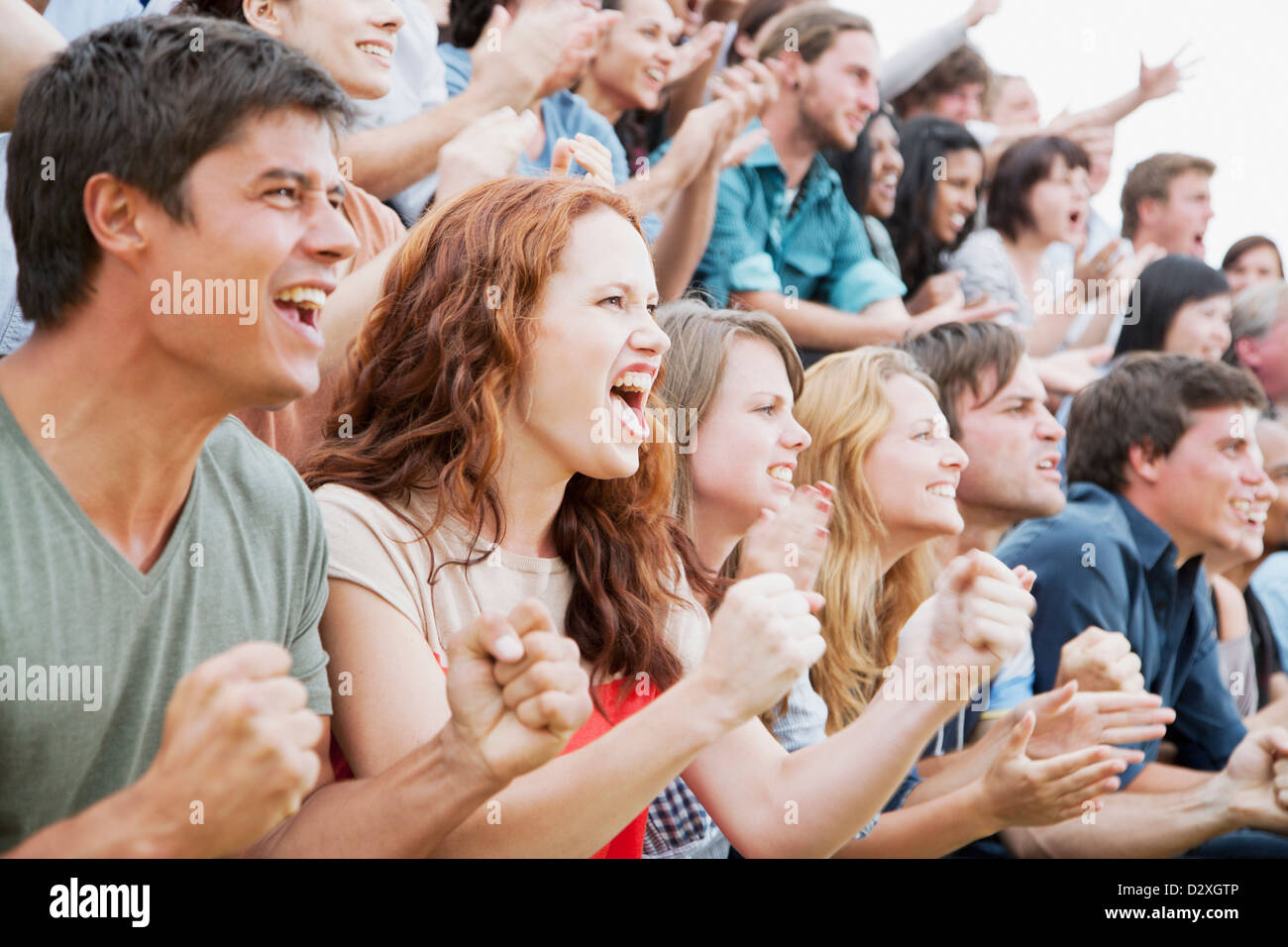 Fans cheering in crowd - Stock Image