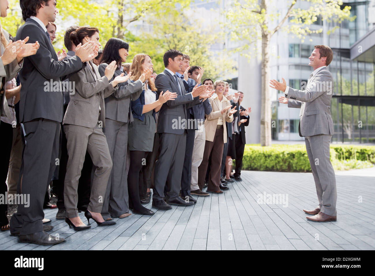 Crowd of business people cheering for businessman - Stock Image