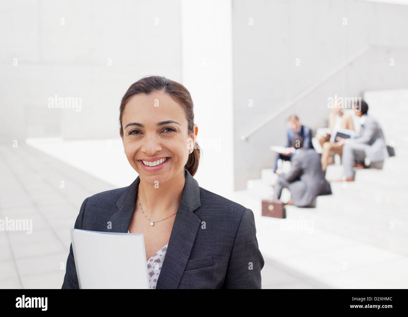 Portrait of confident businesswoman with co-workers in background - Stock Image