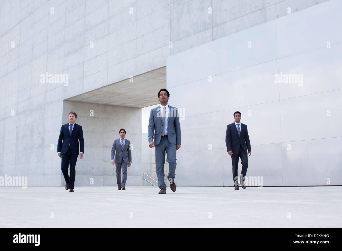 Businessmen leaving modern cultural center - Stock Image