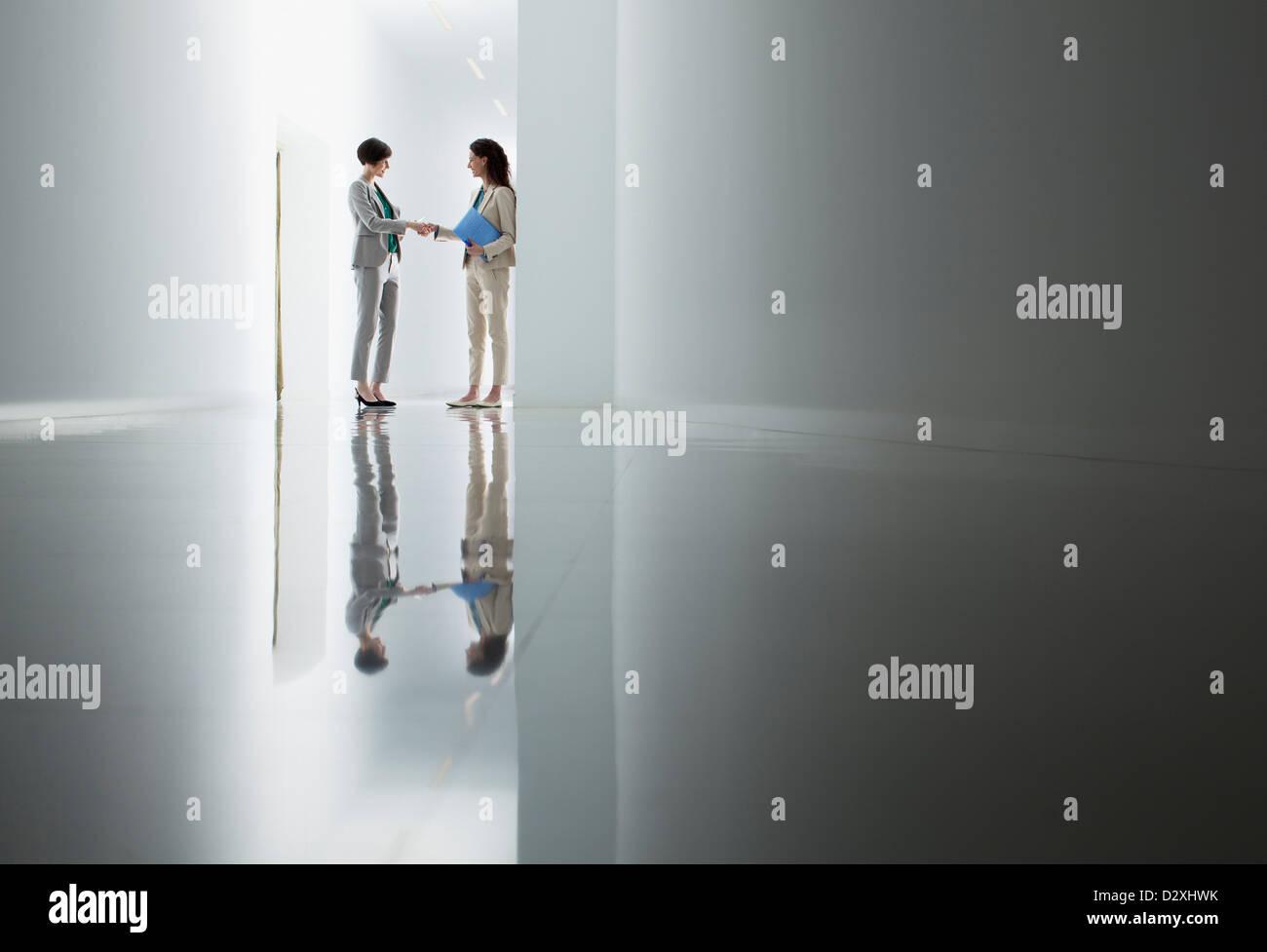 Businesswomen shaking hands in corridor - Stock Image