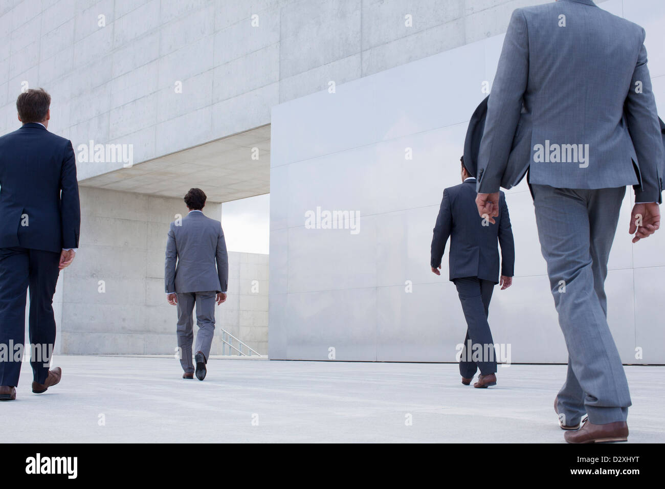 Businessmen walking toward cultural center - Stock Image