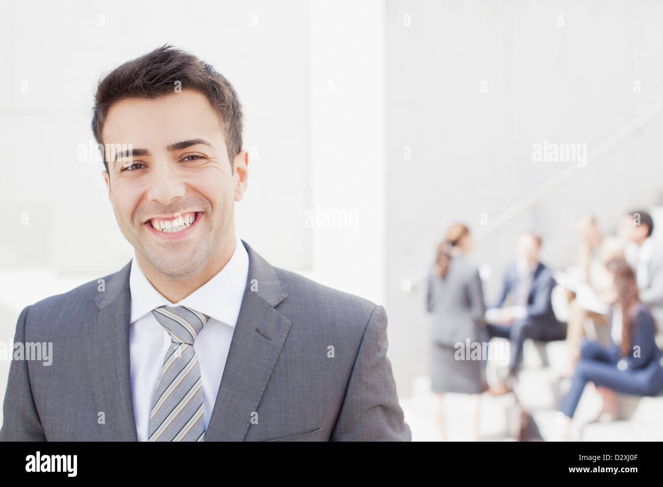 Portrait of smiling man with co-workers in background Stock Photo