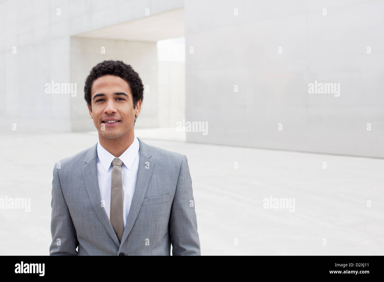 Portrait of smiling businessman standing outside cultural center - Stock Image