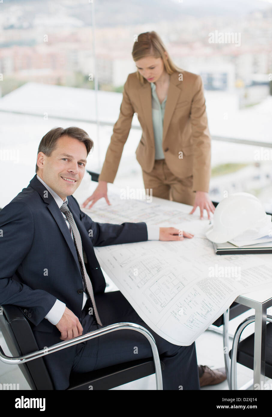 Portrait of confident architect reviewing blueprints with co-worker - Stock Image