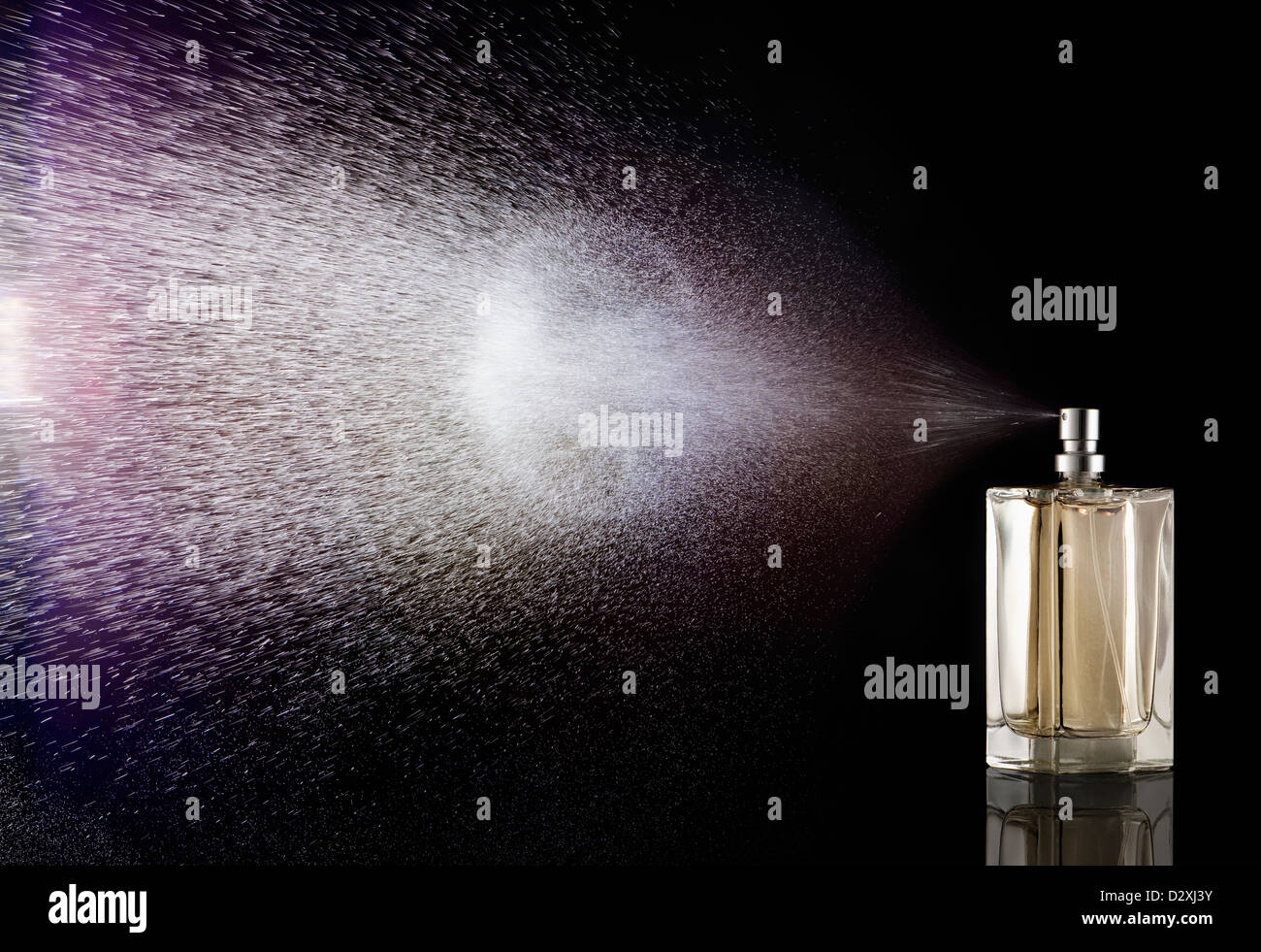 Perfume spraying from bottle - Stock Image