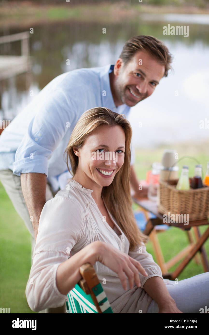 Portrait of smiling couple enjoying picnic at lakeside Stock Photo