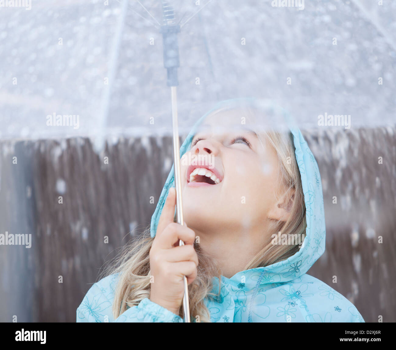 Close up of girl under umbrella looking up at downpour - Stock Image