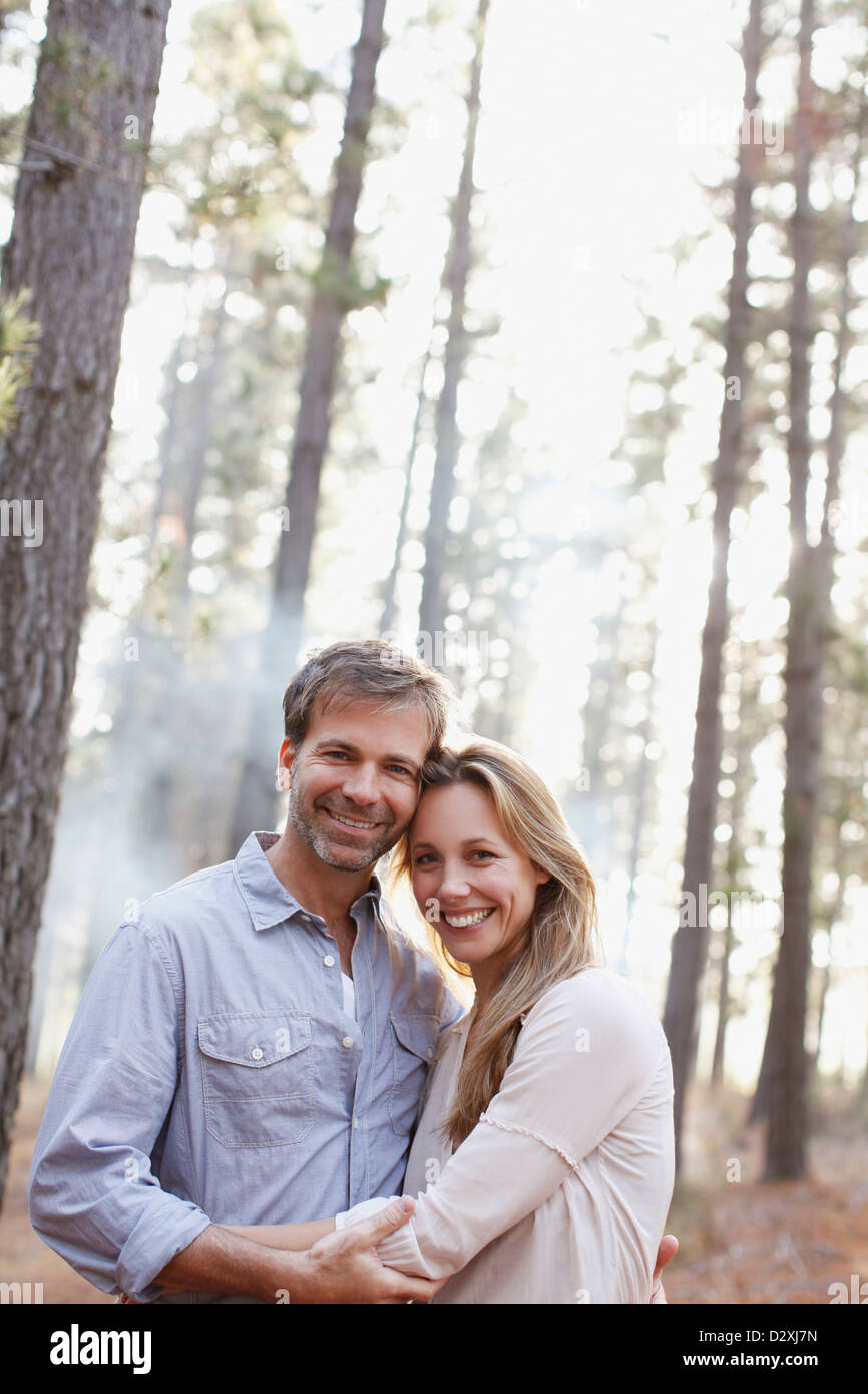 Portrait of smiling couple in woods - Stock Image