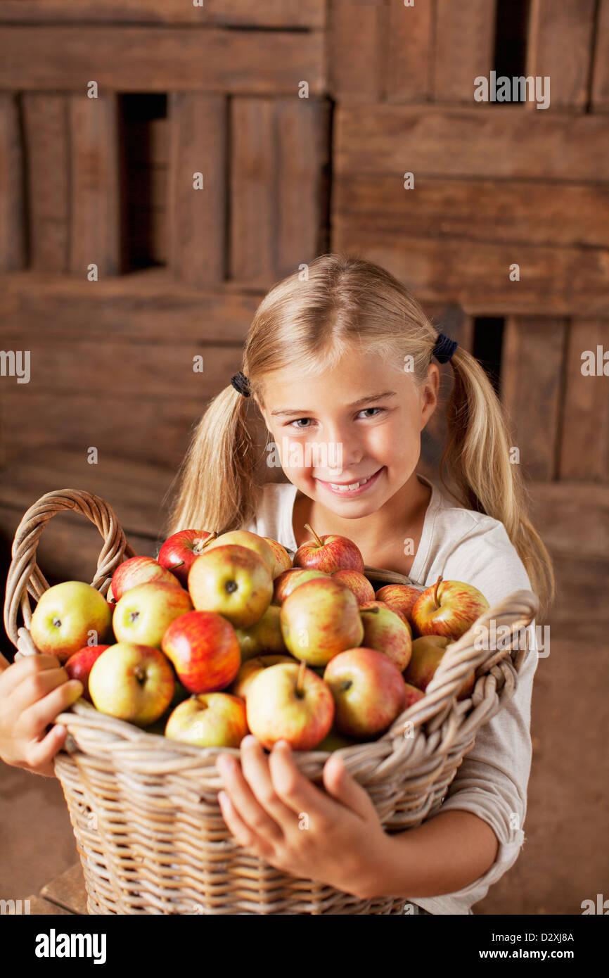 Portrait of smiling girl holding bushel of apples - Stock Image