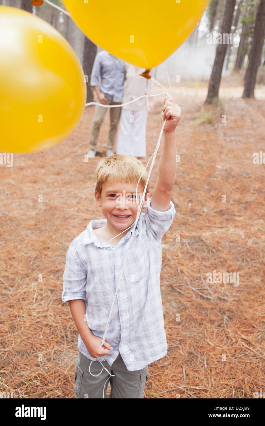 Portrait of smiling boy holding balloons in woods with parents in background - Stock Image