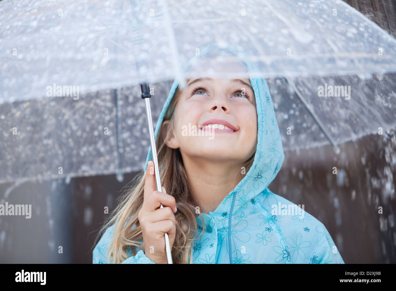 Close up of smiling girl under umbrella in downpour - Stock Image