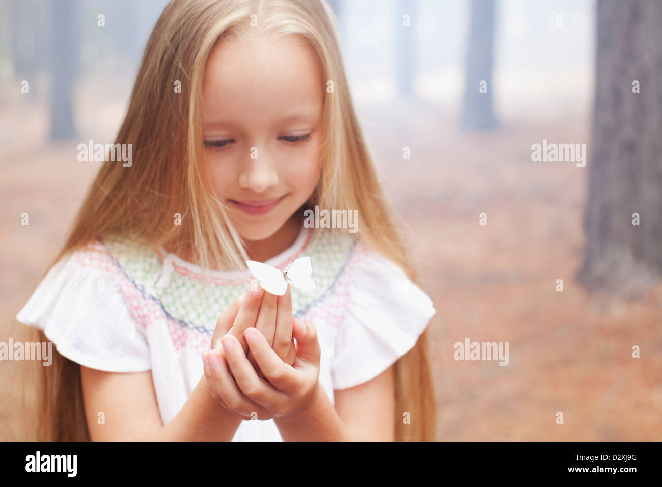 Close up of girl holding butterfly in woods - Stock Image