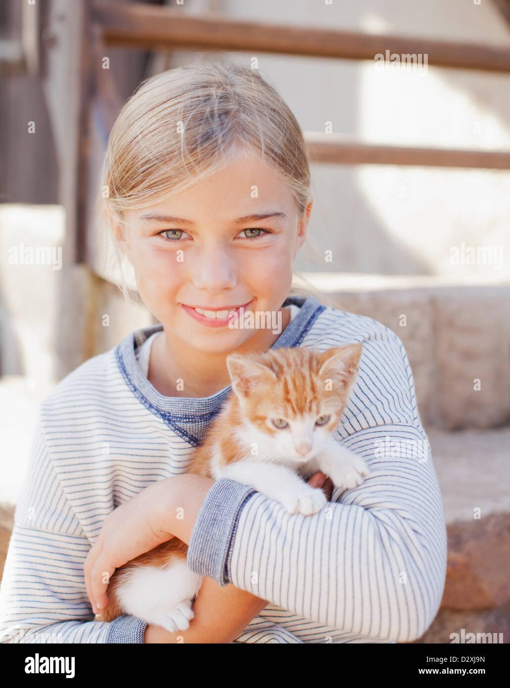 Portrait of smiling girl holding kitten - Stock Image