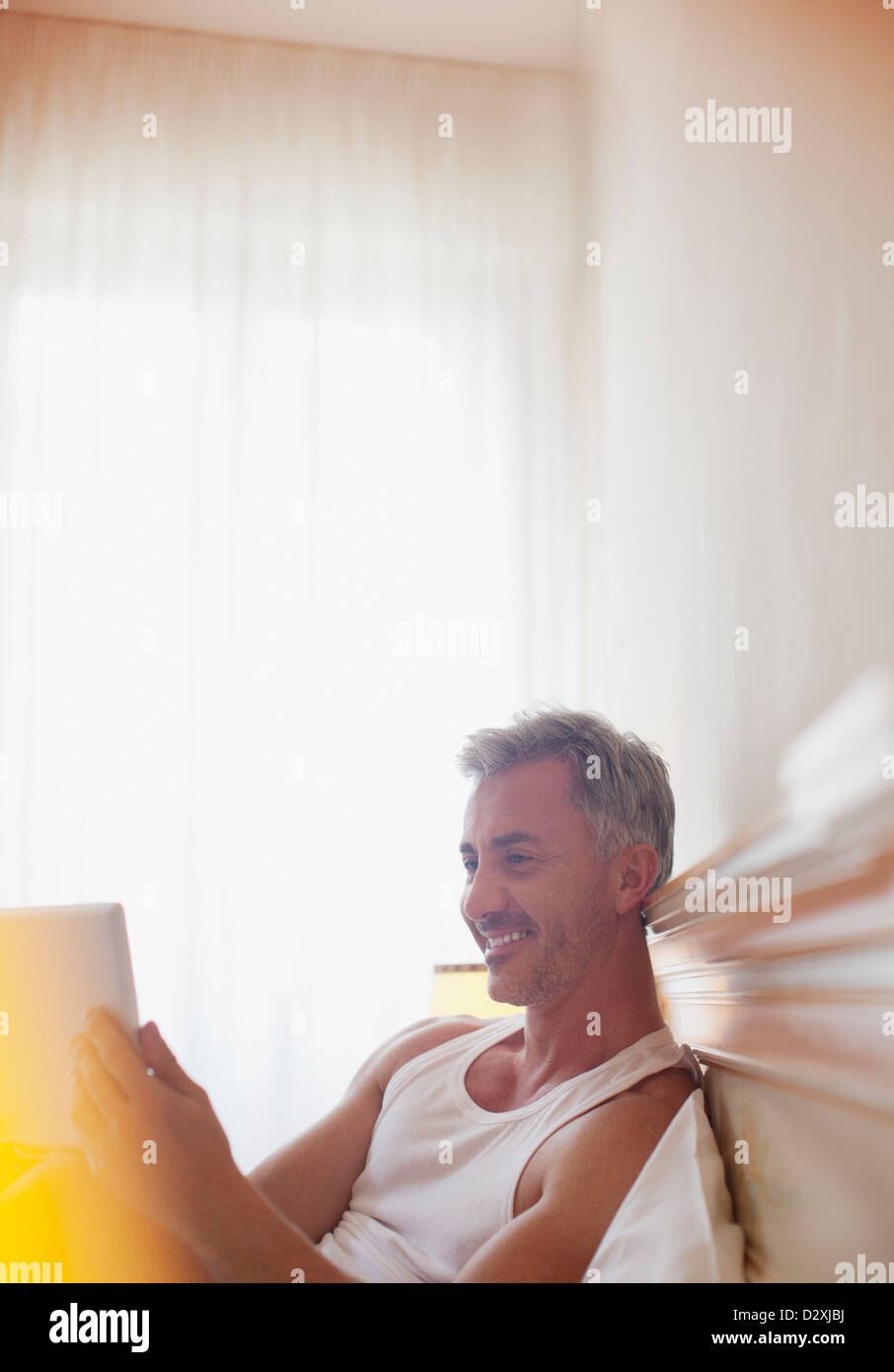 Smiling man using digital tablet in bed - Stock Image