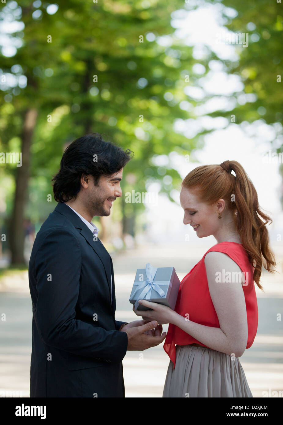 Man giving woman gift in park - Stock Image