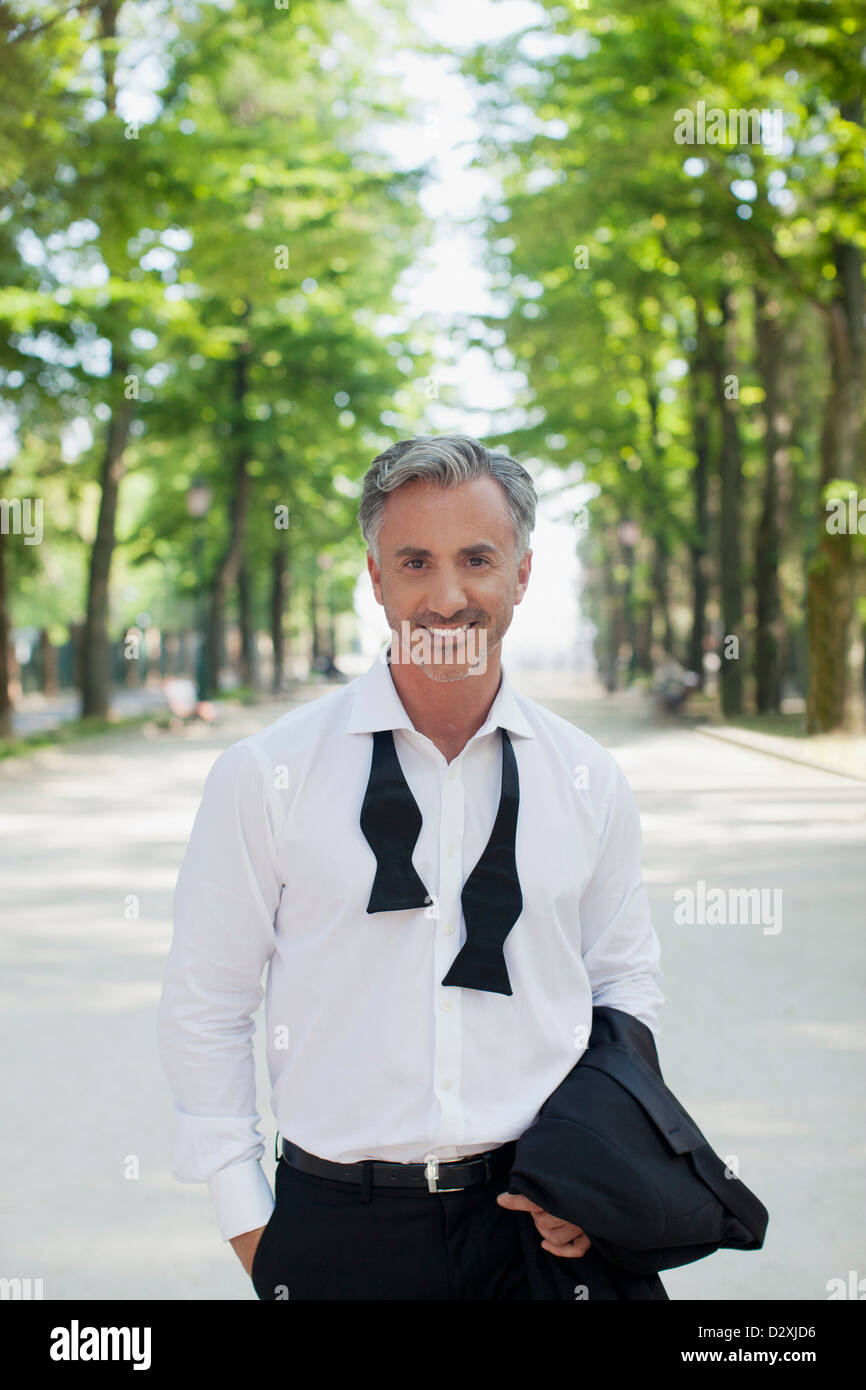 Portrait of well-dressed man in park - Stock Image