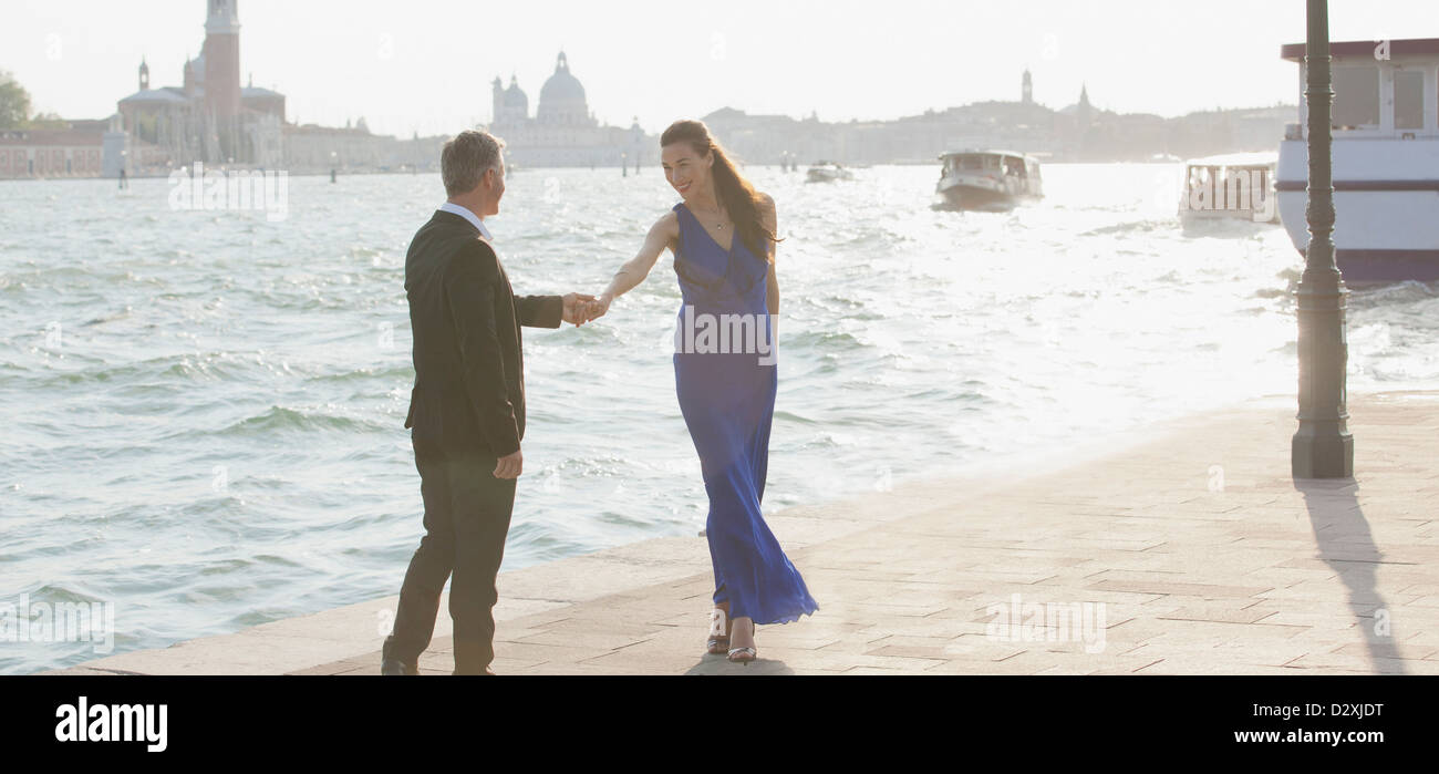 Well-dressed man and woman at waterfront in Venice - Stock Image