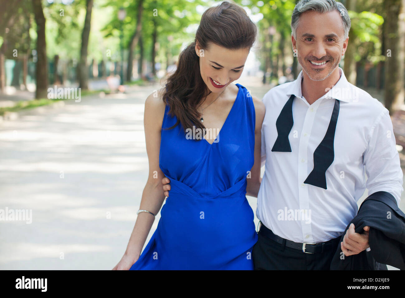 Smiling well-dressed couple in park - Stock Image