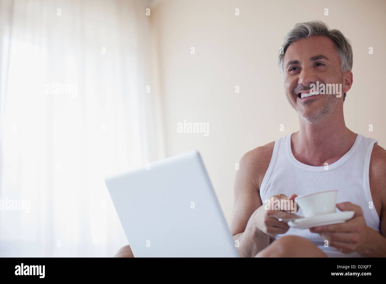 Smiling man drinking coffee and using laptop in bedroom - Stock Image