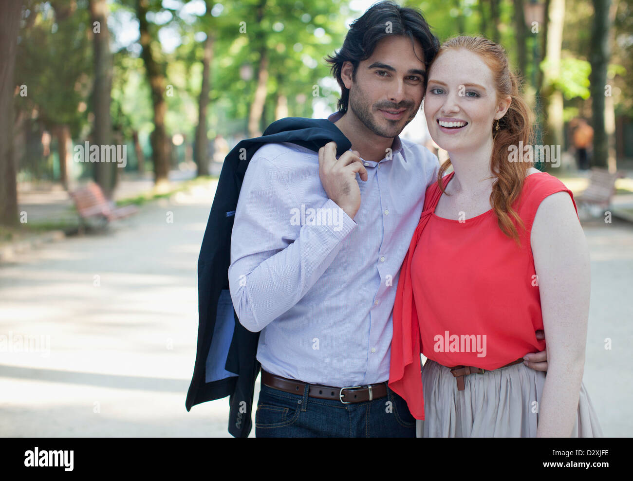 Portrait of smiling couple in park - Stock Image