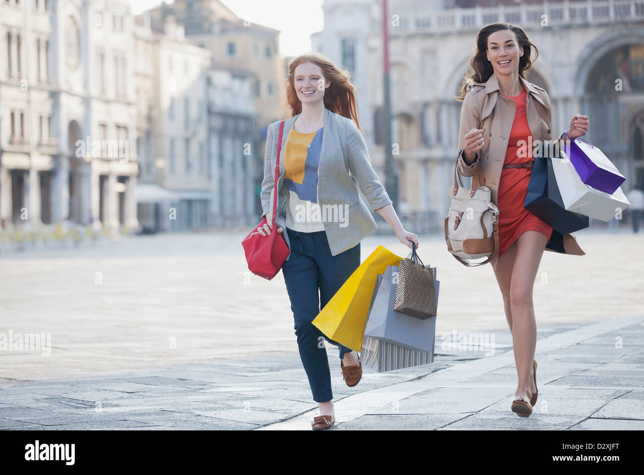 Happy friends with shopping bags running in St. Mark's Square in Venice - Stock Image