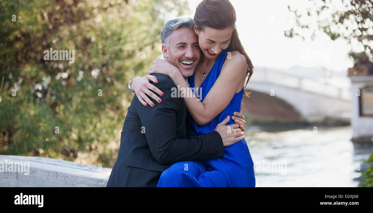 Happy well-dressed couple hugging - Stock Image