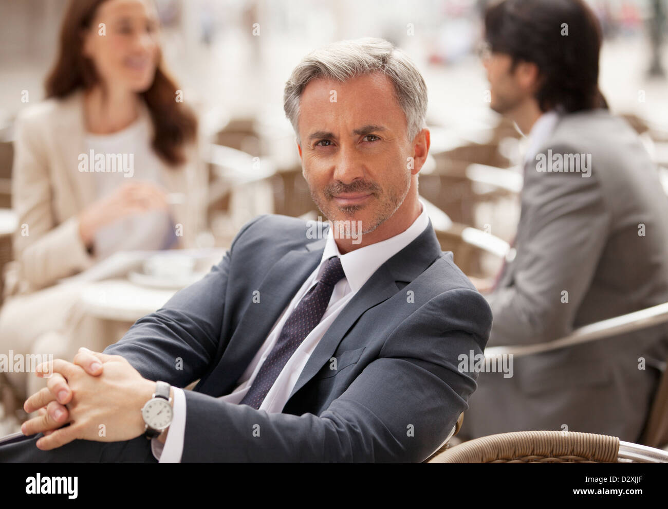 Portrait of smiling businessman at sidewalk cafe with co-workers in background - Stock Image