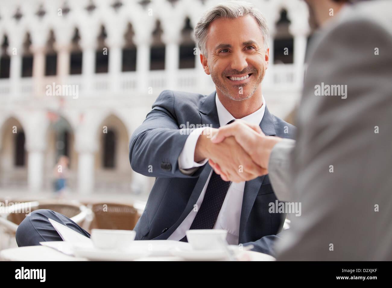 Smiling businessmen shaking hands at sidewalk cafe - Stock Image