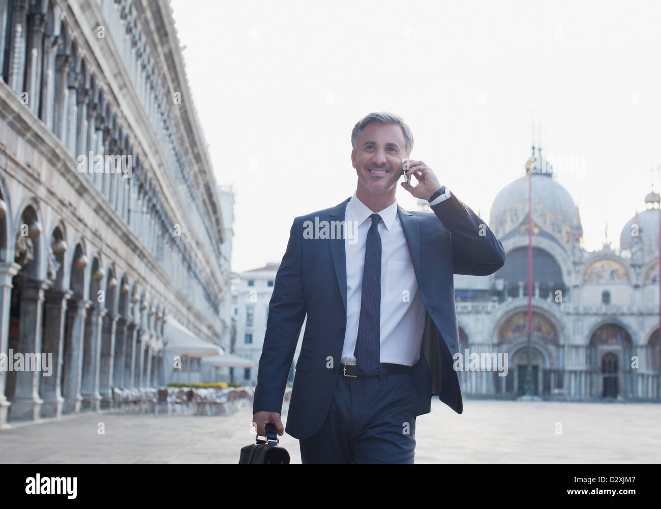 Smiling businessman talking on cell phone and walking through St. Mark's Square in Venice - Stock Image