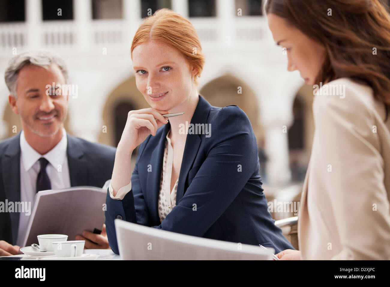 Portrait of smiling businesswomen working with co-workers at sidewalk cafe - Stock Image