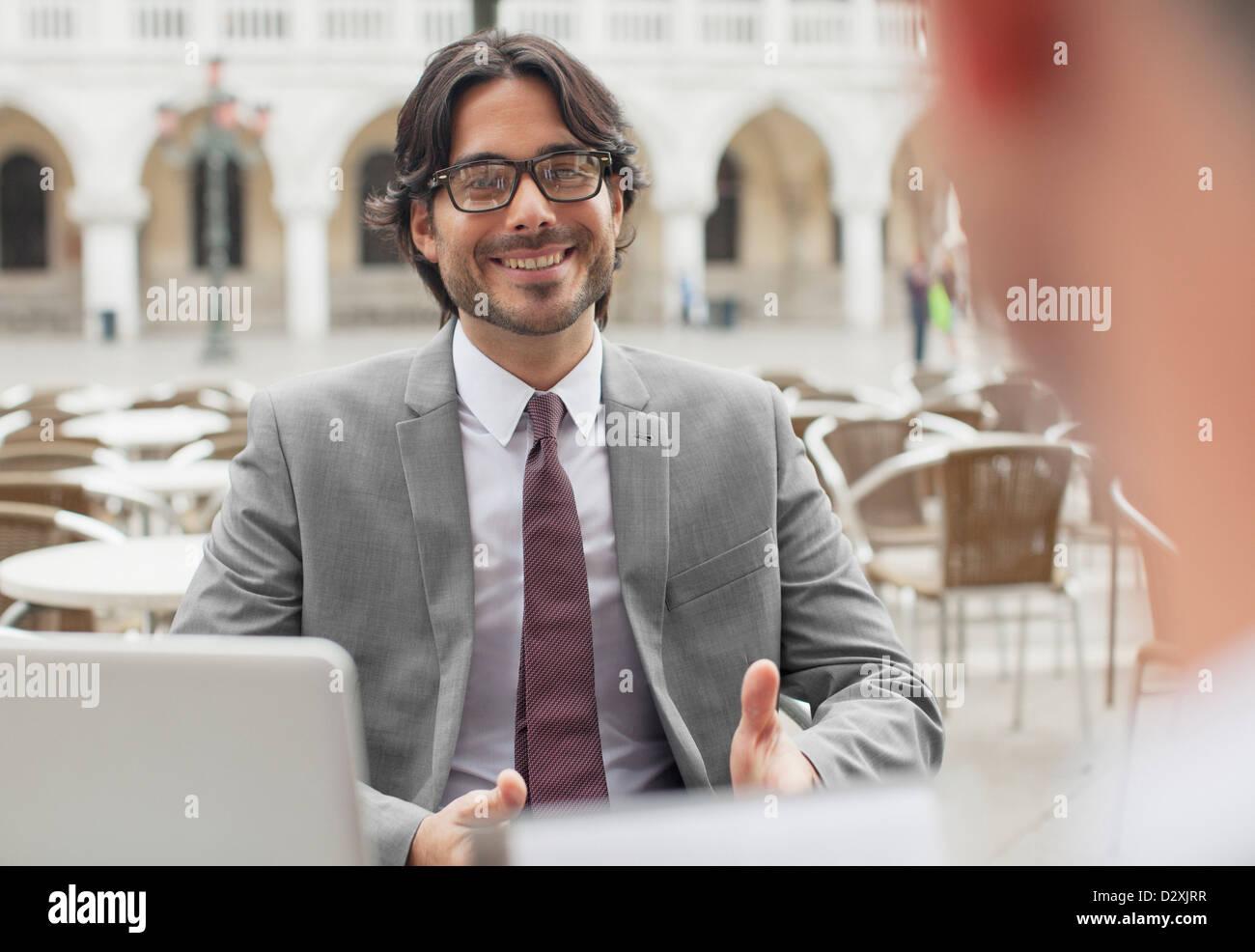 Smiling businessman talking to co-worker at sidewalk cafe - Stock Image