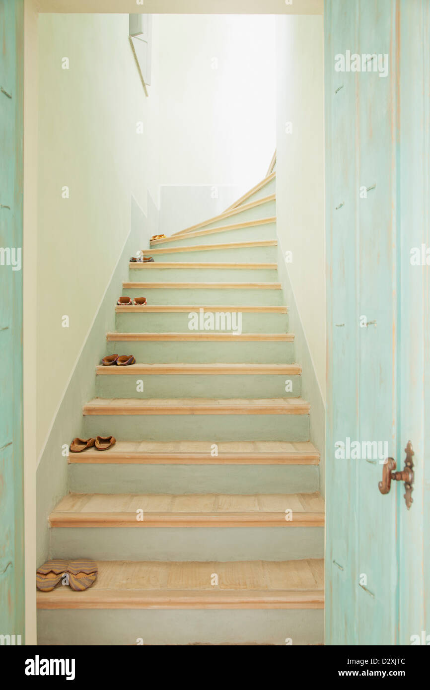 Slippers lining stairs - Stock Image