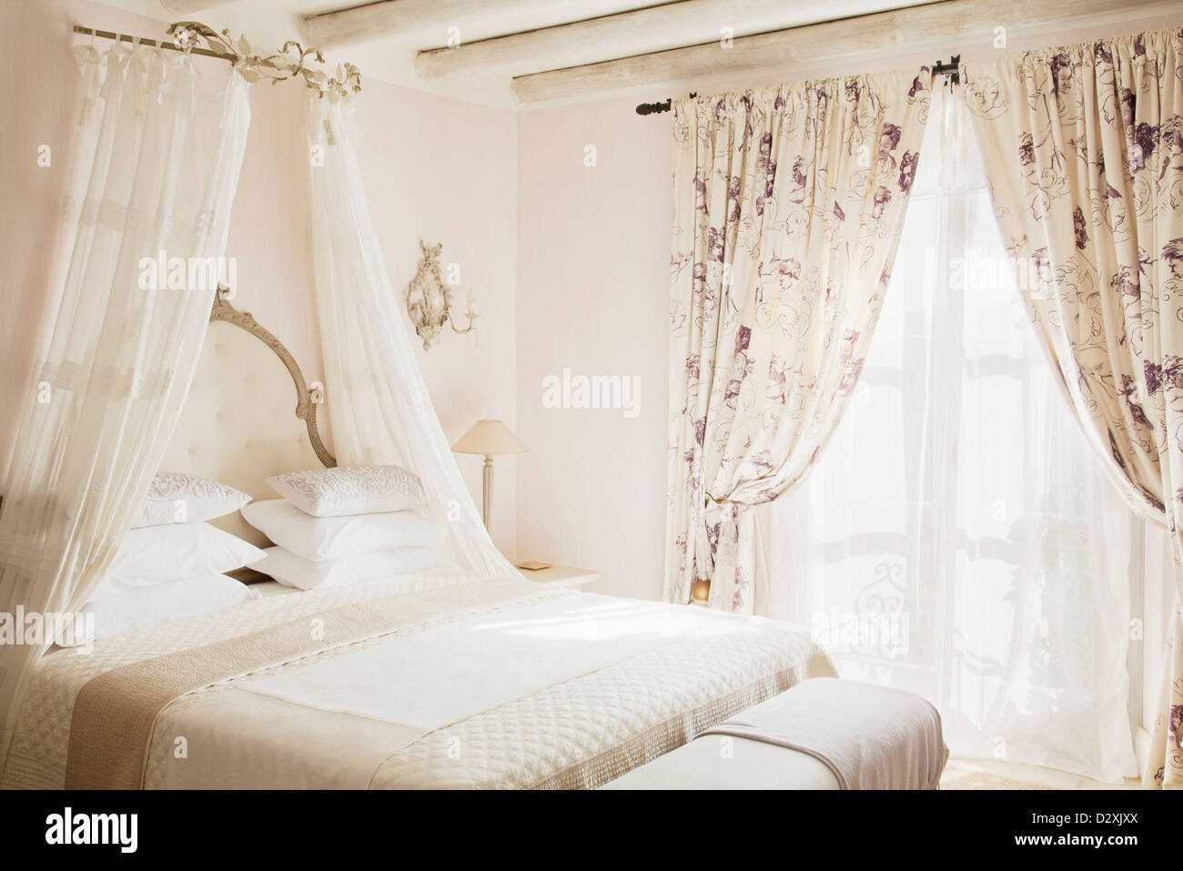 Bed with canopy in luxury bedroom - Stock Image