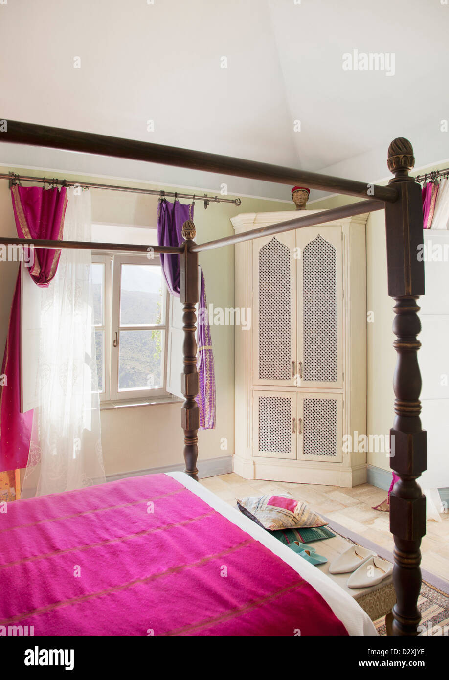 Four poster bed with purple bedding in bedroom - Stock Image