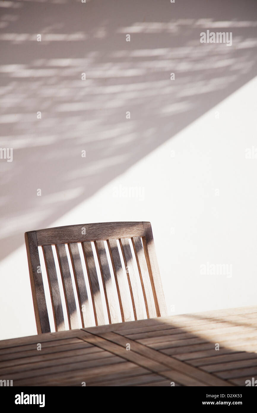 Wooden table and chair in sunlight - Stock Image