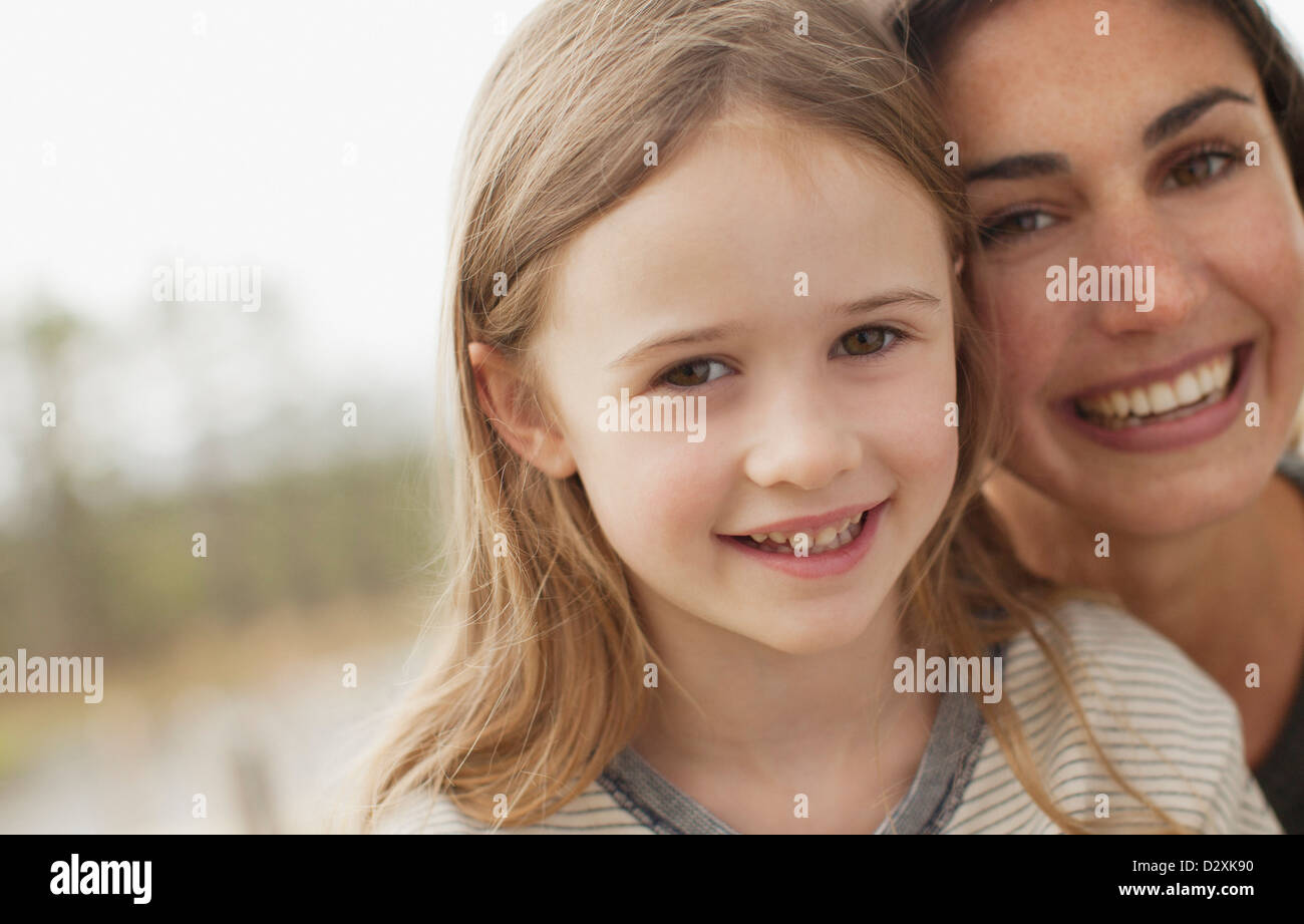 Close up portrait of smiling mother and daughter - Stock Image